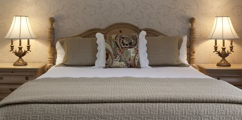 close up image of king size bed with contemporary bedding linens