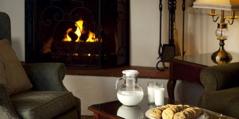 Lobby area with fire in fireplace displaying milk and cookies served in th eevening