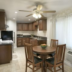 Harbor suite dinng area with table and four chiars and renovated kitchen with updated appliances and kitchen amenities