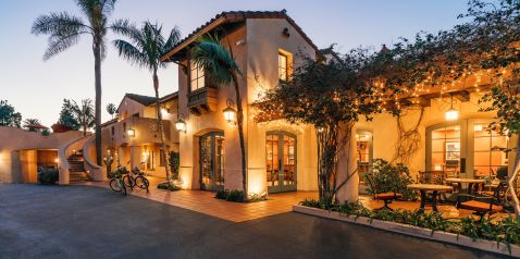 Twilight exterior with twinkle lights with palm trees and cascading flowers