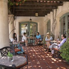 various guests, both men and women, enjoying a ghlas sof wine on the outside patio under the vine covered Pergola