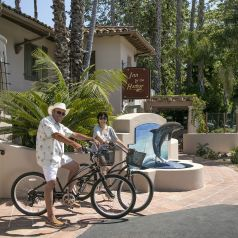 Exterior image in front of the Mediterranean style hotel with man and woman on bicycles which are offered as a complimentary amenity