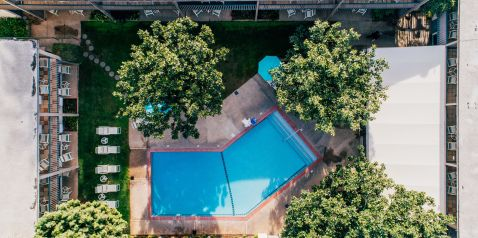 aerial view of pool courtyard with lounge chairs and lush foliage