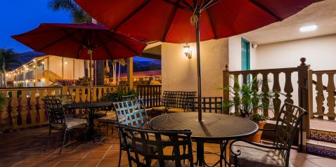 Upstairs twilight patio image with tables and patio umbrellas